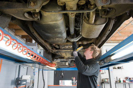 underneath: A mechanic is checking the technical state underneath a lifted car on a bridge in a garage  Stock Photo