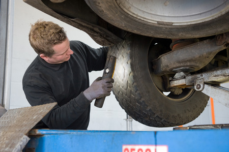 servicing: A mechanic is checking the profile of a tyre from a lifted car on a bridge in a garage