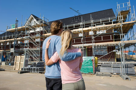 house under construction: Young couple looking at newly built houses on construction site