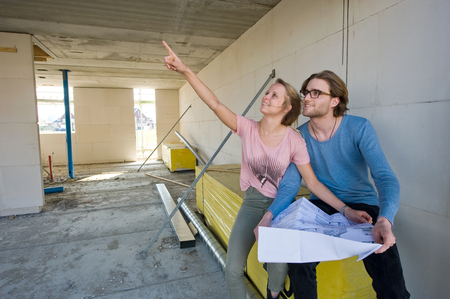 Young couple with blueprint is looking in the livingroom how their new home is being built photo