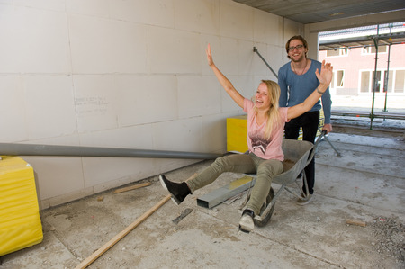 Young couple is happy and having fun with a wheelbarrow in their new built home photo