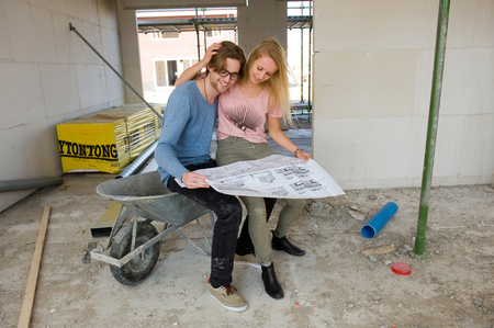 house under construction: Young couple with blueprint is looking happily in the living room how their new home