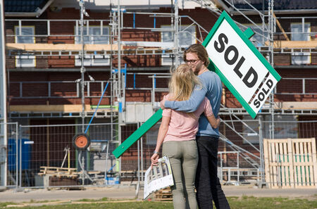 Young couple with blueprint is happy in front of their new built house they just bought photo
