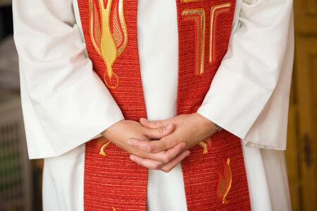 Een vrouwelijke priester vouwt haar handen tijdens het bidden Stockfoto