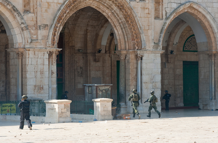 israelis: JERUSALEM, ISRAEL - OCT 08: Israeli military police officers running in front of the Al-aqsa mosque on the temple-square in Jerusalem during fightings with muslims, October 08 in Israel