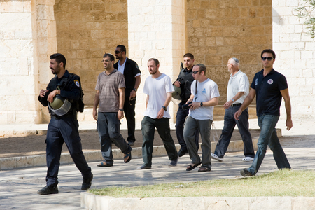 israelis: JERUSALEM, ISRAEL - OCT 08: Jews protected by security officers are walking on the temple-square and want to pray, this is the reason of the tensions and rioting with muslims , October 08 in Israel