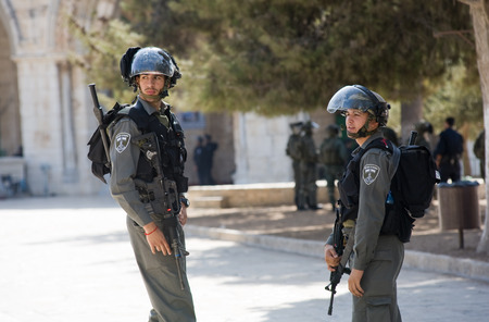 armed: JERUSALEM, ISRAEL - OCT 08: Israeli police officers in front of the Al-aqsa mosque on the temple-square in Jerusalem keeping the security after fightings with muslims, October 08 in Israel Editorial