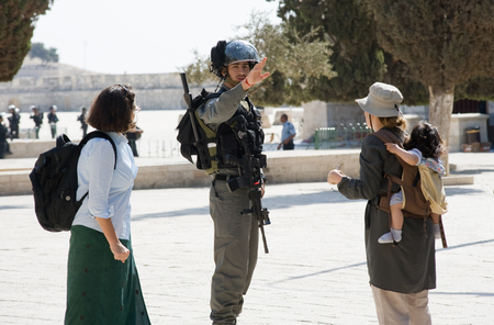 israelis: JERUSALEM, ISRAEL - OCT 08: Israeli police officer tells tourists to go backward on the temple-square in Jerusalem during religious fightings with muslims, October 08 in Israel