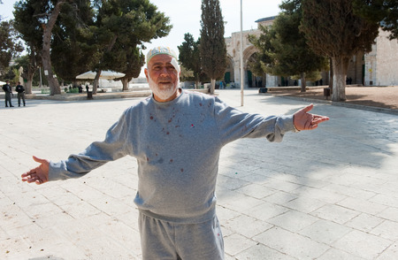 israelis: JERUSALEM, ISRAEL - OCT 08: A wounded muslim man is spreading his arms after fighting with Israeli officers in front of the al-aqsa mosque on the temple-mount in Jerusalem, October 08 in Israel