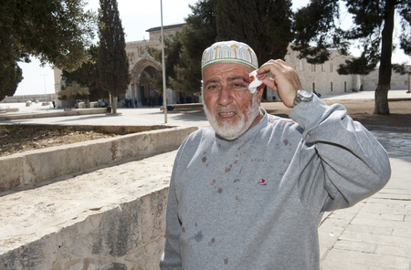 israelis: JERUSALEM, ISRAEL - OCT 08: A wounded muslim is showing his wound after fighting with Israeli officers in front of the al-aqsa mosque on the temple-mount in Jerusalem, October 08 in Israel