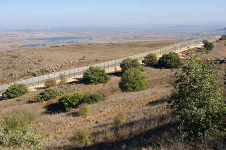 the golan heights: The fence of the border between Israel and Syria as seen from a hill on the Golan Heights about 10 kilometers southsouth-east of the city Al Quneitra