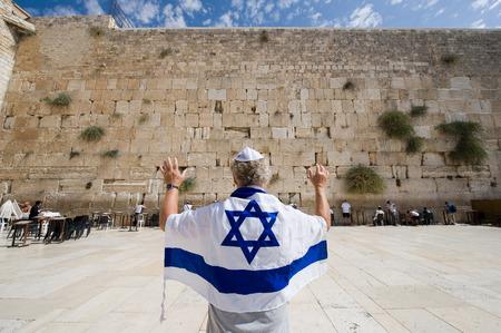 イスラエル、エルサレム - 2014 年 10 月 7 日: Israelian の旗、エルサレムの旧市街の西側の壁の前で育った彼の腕を持つ男 報道画像