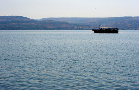 Boat with tourists floating on the sea of Galilee near Capernaum