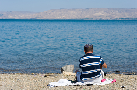 TIBERIAS, ISRAEL - OCT 03, 2014: A jewish man is sitting on the beach if the sea of Galilee just south of Tiberias Editorial