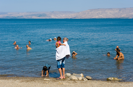 TIBERIAS, ISRAEL - OCT 03, 2014: People are relaxing on the beach and in the sea of Galilee just south of Tiberias