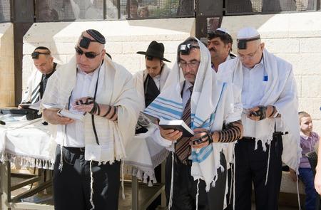 torah: JERUSALEM, ISRAEL - OCT 06, 2014: Jews are reading in the torah during a Bar Mitzvah ritual at the Wailing wall in Jerusalem