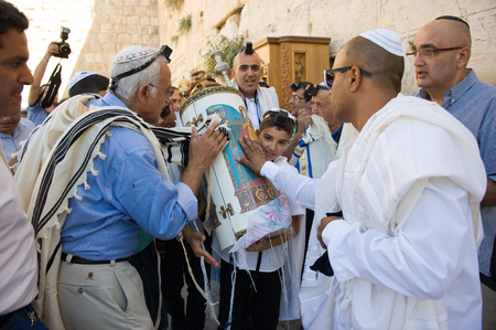 morally: JERUSALEM, ISRAEL - OCT 06, 2014: Bar Mitzvah ritual at the Wailing wall in Jerusalem. A 13 years old boy who has become a Bar Mitzvah is morally and ethically responsible for his decisions and actions