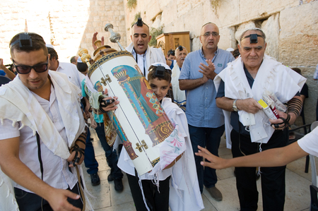 mitzvah: JERUSALEM, ISRAEL - OCT 06, 2014: A 13 years old boy is carrying a torah scroll during a Bar Mitzvah ritual at the Wailing wall in Jerusalem.