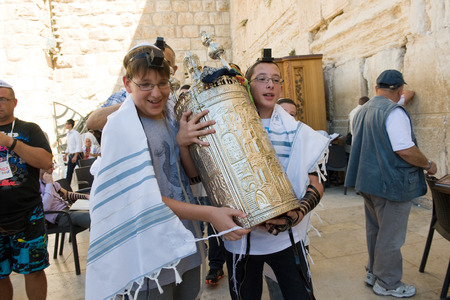 tora: JERUSALEM, ISRAEL - OCT 06, 2014: Two 13 years old boys are carrying a torah scroll during a Bar Mitzvah ritual at the Wailing wall in Jerusalem.