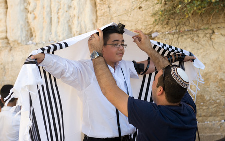 tora: JERUSALEM, ISRAEL - OCT 06, 2014: A jewish man is preparing the tallith of a 13 years old boy before his Bar Mitzvah ritual at the Wailing wall in Jerusalem.
