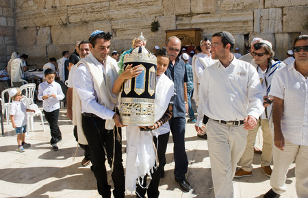 scroll: JERUSALEM, ISRAEL - OCT 06, 2014: Bar Mitzvah ritual at the Wailing wall in Jerusalem. A 13 years old boy who has become a Bar Mitzvah is morally and ethically responsible for his decisions and actions