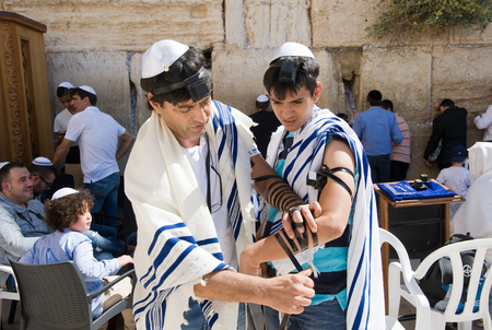 tefillin: JERUSALEM, ISRAEL - OCT 06, 2014: A jewish man is preparing the tefillin around the arm of a boy of 13 years old before his Bar Mitzvah ritual at the Wailing wall in Jerusalem. Editorial