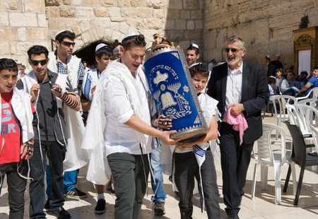 tora: JERUSALEM, ISRAEL - OCT 06, 2014: Bar Mitzvah ritual at the Wailing wall in Jerusalem. A 13 years old boy who has become a Bar Mitzvah is morally and ethically responsible for his decisions and actions