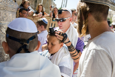 JERUSALEM, ISRAEL - OCT 06, 2014: Bar Mitzvah ritual at the Wailing wall in Jerusalem. A 13 years old boy who has become a Bar Mitzvah is morally and ethically responsible for his decisions and actions