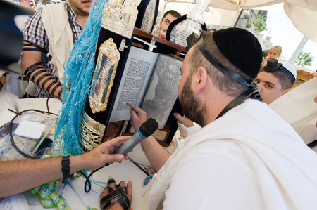 bar mitzvah: JERUSALEM, ISRAEL - OCT 06, 2014: A jewish man is reading from the torah during a Bar Mitzvah ritual at the Wailing wall in Jerusalem.