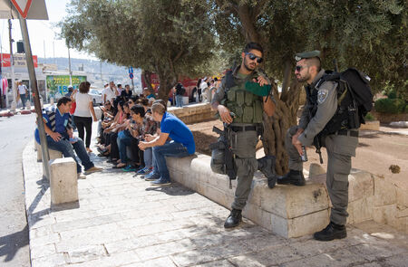 israelis: JERUSALEM, ISRAEL - OCT 06, 2014: Two police officers taking care of the security on the street just outside the Dung gate of the old city. Dung gate is the closest gate to the western wall