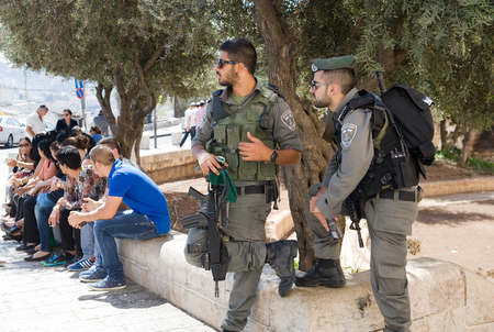 instability: JERUSALEM, ISRAEL - OCT 06, 2014: Two police officers taking care of the security on the street just outside the Dung gate of the old city. Dung gate is the closest gate to the western wall