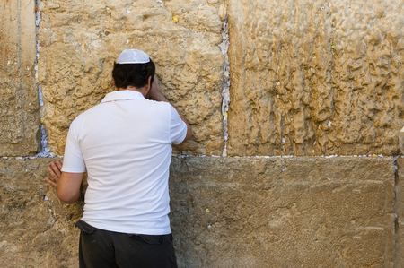 western wall: A jewish man is praying against the western wall in the old city of Jerusalem Stock Photo