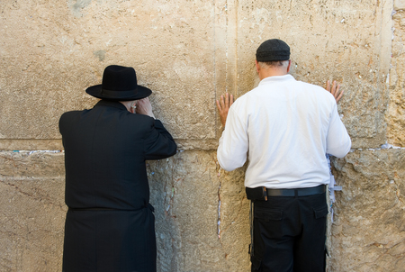 western wall: JERUSALEM, ISRAEL - OCT 06, 2014: Two jewish man are praying against the western wall in the old city of Jerusalem