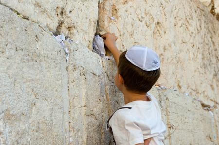 Jeruzalem, Israël - oktober 6, 2014: Een jonge joodse jongen zet een papier met een wens in een spleet tussen de stenen van de westelijke muur in de oude stad van Jeruzalem