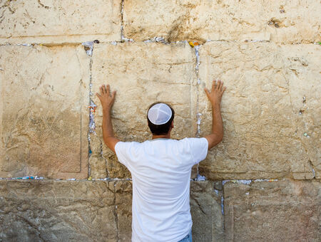 western wall: A jewish man is praying against the western wall in the old city of Jerusalem Editorial