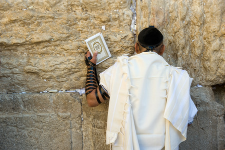 JERUSALEM, ISRAEL - OCT 06, 2014: A jewish man with the torah in his hand is praying against the western wall in the old city of Jerusalem