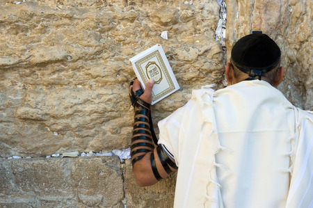 tefillin: JERUSALEM, ISRAEL - OCT 06, 2014: A jewish man with the torah in his hand and tefillin around his arm is praying against the western wall in the old city of Jerusalem