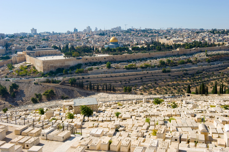 Old jewish graves on the mount of olives in Jerusalem, with on the back the temple mount with the dome of the rock