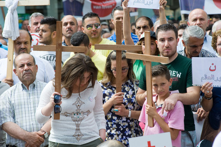 syria peace: ENSCHEDE, THE NETHERLANDS - AUG 03, 2014: During a demonstration organized by suryoye christians against the slaughter of christians in the middle east there is a minut of silence for those who are dead Editorial