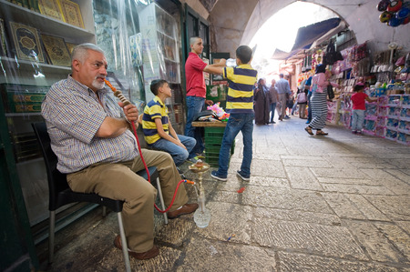waterpipe: JERUSALEM, ISRAEL - OCTOBER 07, 2014: An elderly man is smoking a waterpipe in front of one of the small streets in the old city of Jerusalem Editorial