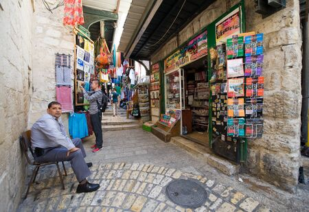 via dolorosa: JERUSALEM, ISRAEL - OCTOBER 07, 2014: A man is sitting outside his shop on the Via Dolorosa, one of the small streets in the old city of Jerusalem