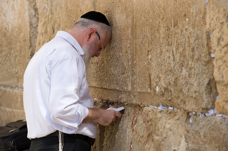 JERUSALEM, ISRAEL - OCT 07, 2014: A jewish man with the torah in his hands is praying in front of the western wall in the old city of Jerusalem