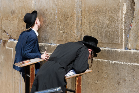JERUSALEM, ISRAEL - OCT 07, 2014: Two jewish men are praying in front of the western wall in the old city of Jerusalem