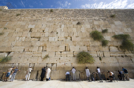 JERUSALEM, ISRAEL - OCT 07, 2014: Jewish men are praying in front of the western wall in the old city of Jerusalem Editorial