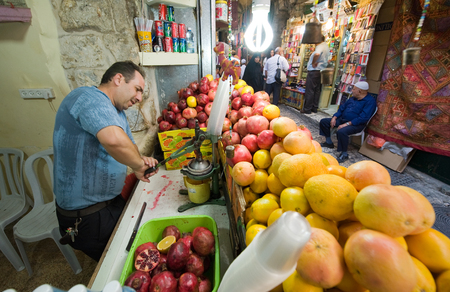 israel agriculture: JERUSALEM, ISRAEL - OCTOBER 07, 2014: A man is making juice from a pomegranate in one of the small streets in the old city of Jerusalem