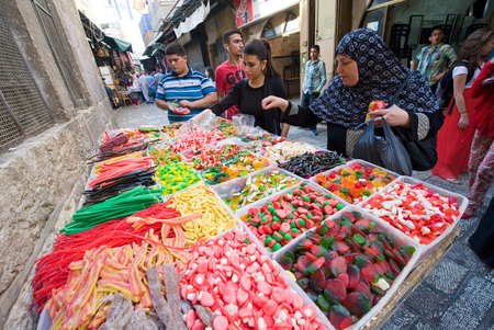 JERUSALEM, ISRAEL - OCTOBER 07, 2014: Woman are watching and buying sweets at a candy store in one of the small streets in the old city of Jerusalem