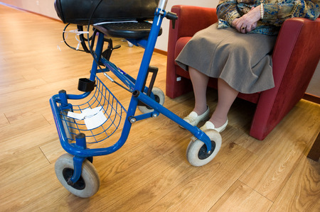 eldercare: ENSCHEDE, THE NETHERLANDS - 10 NOV, 2014: A woman with a walking frame sitting in a chair in a home for elderly Stock Photo