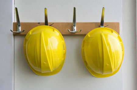 safety wear: Two helmets hanging on coat hangers on a construction place Stock Photo