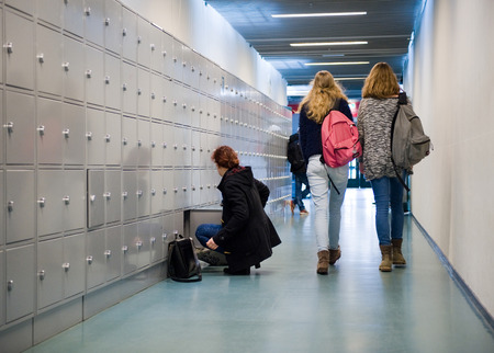 ENSCHEDE, THE NETHERLANDS - 02 FEB, 2015: Students are walking through a hallway with lockers on a high school Редакционное