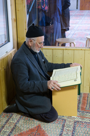 coran: ENSCHEDE, THE NETHERLANDS - 08 FEBRUARI, 2015: A man is reading in the koran in a seperate room in a small mosque in the Netherlands